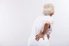 Uma mulher idosa com dor traseira Fotografia de Stock Royalty Free