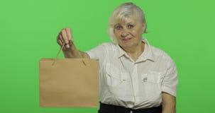 Uma mulher idosa com saco de compras Compras presentes Chave do croma video estoque