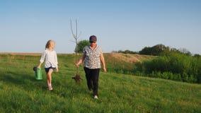 Uma mulher idosa com uma neta de 6 anos está indo plantar uma árvore Pessoas adultas ativas, família forte e vídeos de arquivo
