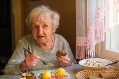 Uma mulher idosa idosa come o assento na tabela em sua casa cozinhar imagem de stock