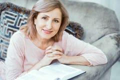 Uma mulher idosa da aparência europeia reza perto da Bíblia imagens de stock