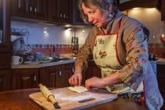 Uma mulher idosa em um avental prepara a torta fotografia de stock
