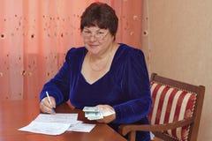 Uma mulher idosa enche recibos Fotografia de Stock Royalty Free