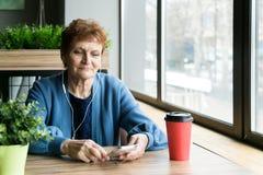 Uma mulher idosa escuta a música em fones de ouvido fotos de stock
