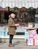 Uma mulher idosa está lendo um jornal fora de uma loja do jornal No contador são os compartimentos e os jornais fotografia de stock royalty free