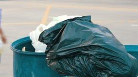 Uma mulher idosa joga para fora um pacote completo do lixo na lata de lixo filme