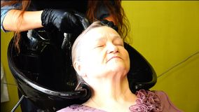 Uma mulher idosa lava sua cabeça no dissipador antes dos procedimentos filme
