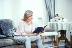 Uma mulher idosa na roupa da casa está sentando em Sofa With um livro em suas mãos fotografia de stock