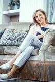 Uma mulher idosa na roupa da casa está sentando em Sofa With um livro em suas mãos imagem de stock