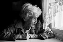 Uma mulher idosa olha longingly para fora a janela loneliness imagens de stock