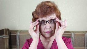 Uma mulher idosa põe sobre vidros video estoque