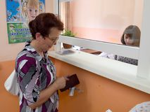 Uma mulher idosa paga por um apartamento na bilheteira Foto de Stock Royalty Free