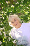 Uma mulher idosa perto da árvore de florescência Foto de Stock Royalty Free