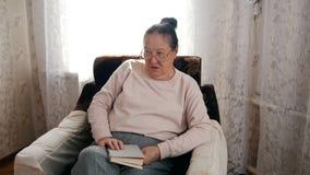 Uma mulher idosa que senta-se em uma cadeira e que lê um livro, olhando com desprezo foto de stock