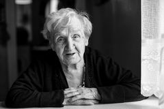 Uma mulher idosa que senta-se na tabela fotos de stock