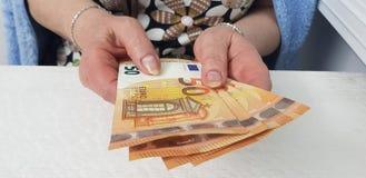 Uma mulher idosa realiza dinheiro do dinheiro de ambas as mãos no euro- imagens de stock