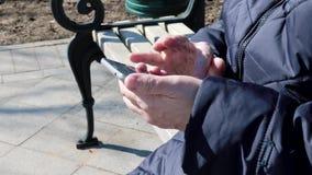 Uma mulher idosa superior que senta-se em um banco no ar livre do parque e que usa o smartphone de batida - está usando o smartph vídeos de arquivo