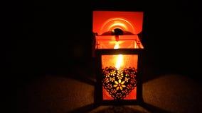 Uma mulher ilumina uma vela de um fósforo em uma lanterna elétrica vermelha em um fundo preto vídeos de arquivo