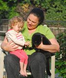 Uma mulher introduz uma criança a um gato preto Imagem de Stock Royalty Free