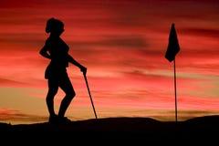 Uma mulher joga o golfe de encontro a um por do sol brilhante Foto de Stock Royalty Free