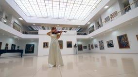 Uma mulher joga o violino apenas, ao estar em uma sala com pinturas em paredes video estoque