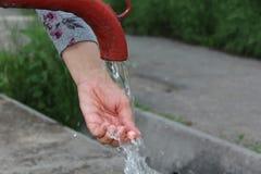 Uma mulher lava sua mão Bomba de mão velha da água no centro da cidade moderna Imagens de Stock Royalty Free