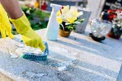 Uma mulher limpa a sepultura imagens de stock
