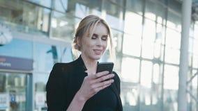 Uma mulher loura bonita em um equipamento preto formal está pela entrada do aeroporto, usa seu telefone celular, obtém o texto filme