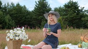 Uma mulher loura bonita nova em um chapéu e em um vestido está bebendo a limonada de uma lata ao sentar-se em uma manta no verde video estoque