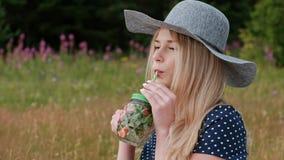 Uma mulher loura bonita nova em um chapéu e em um vestido está bebendo a limonada de uma lata ao sentar-se em uma manta no verde vídeos de arquivo