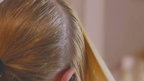 Uma mulher loura com cabelo longo está penteando na frente de um espelho, preparando sua cabeça para raizes colorindo do cabelo filme