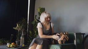 Uma mulher loura está muito feliz jogar com seu cão Yorkshire terrier às mãos de uma menina feliz na sala de visitas vídeos de arquivo