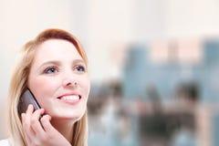 Uma mulher loura nova bonita que faz um telefonema com espaço da cópia Fotografia de Stock