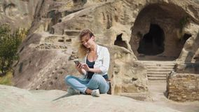 Uma mulher loura nova com a beleza natural, sentando-se na posição dos lótus sobre uma pedra e datilografando uma mensagem sobre  video estoque