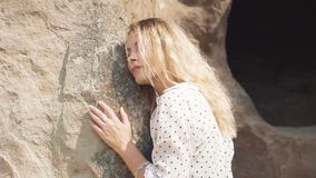 Uma mulher loura nova com uma cara bonita inclinada contra as rochas da cidade antiga Uplistsikhe A menina escuta filme