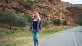 Uma mulher loura nova de sorriso na roupa ocasional simples nas calças de brim e em uma camiseta está andando ao longo da estrada video estoque
