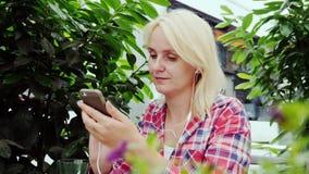 Uma mulher loura nova está descansando em um café no terraço do verão Usa um smartphone video estoque