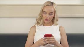 Uma mulher louro-de cabelo encantador está sentando-se no sofá com o telefone Olha a tela, tipos algo Sua cara video estoque