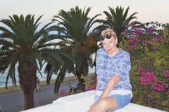 Uma mulher madura contra um fundo das palmeiras Foto de Stock Royalty Free