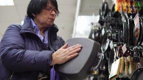Uma mulher madura escolhe uma frigideira do ferro fundido no supermercado video estoque
