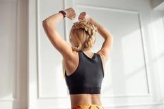 Uma mulher magro nova com um corpo atlético com o cabelo louro longo, vestido na parte superior do preto do sportswear está para  fotografia de stock