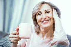 Uma mulher mais de 50 anos de aparência europeia que descansam em casa o chá bebendo imagens de stock