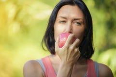 Uma mulher mais idosa está comendo a maçã após o exercício para tomar do fotografia de stock royalty free