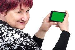 Uma mulher mais idosa que guarda o telefone celular pisc na câmera imagens de stock