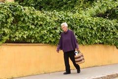 Uma mulher mais idosa que venha da loja imagens de stock royalty free