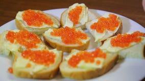 Uma mulher mancha o caviar vermelho com uma colher dos canapes com manteiga entre o canpe pronto em uma placa branca filme