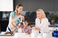 Uma mulher, uma menina e uma mulher idosa estão preparando-se para tentar uma torta caseiro que a mulher coza foto de stock royalty free