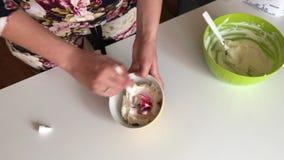 Uma mulher mistura o queijo macio com uma colher Para preparar o creme para o bolo Colora??o de alimento adicionada video estoque