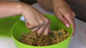 Uma mulher mistura vigorosamente uma migalha da cookie com o leite condensado Cozinhando princ?pios para PNF do bolo video estoque