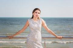Uma mulher modelo encantador em um fundo emocionante azul brilhante do mar A menina magnífica está em férias no mar fotografia de stock